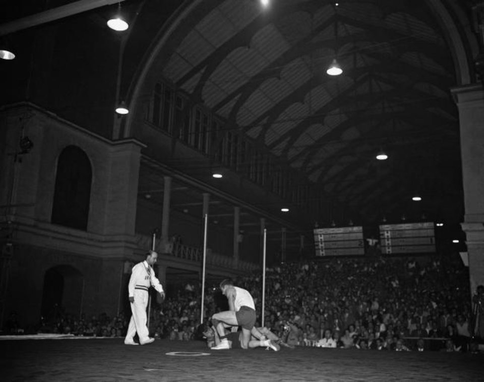 Photo -  American Danny Hodge (white shirt) is shown beating Russian G. Skhirtladze in the final round of Olympic freestyle middleweight wrestling on Dec. 1, 1956, in Melbourne, Australia. In the final placing, the American was second and the Russian third. [AP Photo]