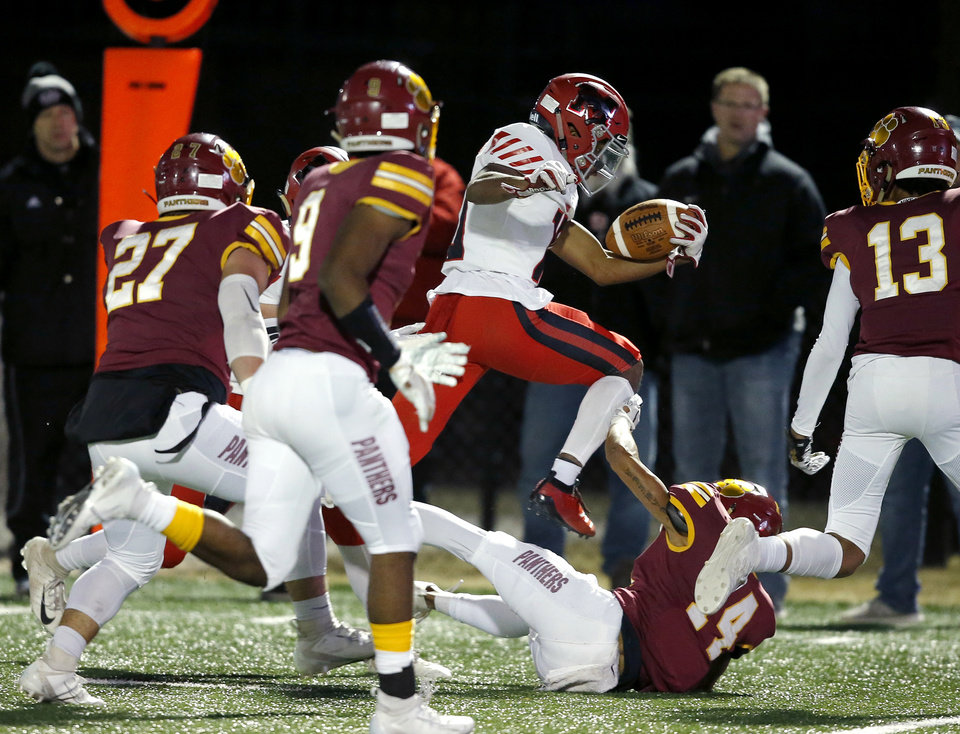 Photo - Mustang's Khary Brown leaps of Putnam City North's Jaramiah Harrison during a high school football game between Putnam City North and Mustang in Oklahoma City, Friday, Nov. 1, 2019.  [Bryan Terry/The Oklahoman]