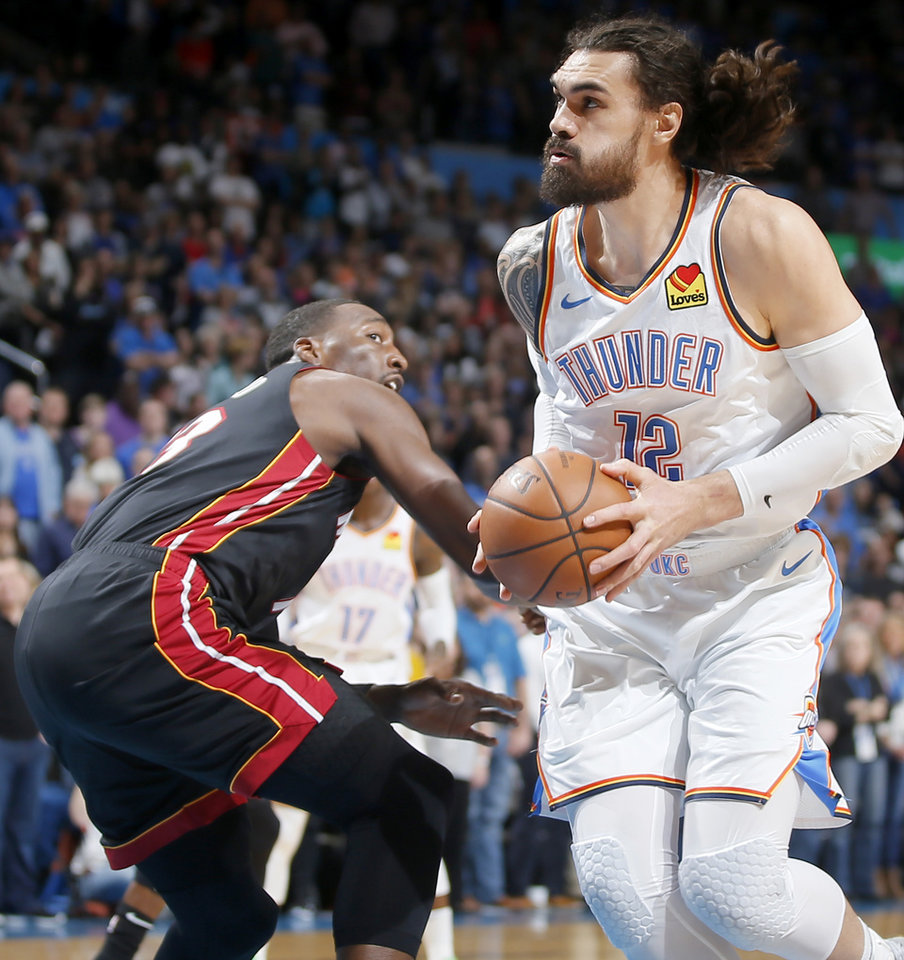 Photo - Oklahoma City's Steven Adams (12) moves past Miami's Bam Adebayo (13) during an NBA basketball game between the Oklahoma City Thunder and the Miami Heat at Chesapeake Energy Arena in Oklahoma City, Monday, March 18, 2019. Photo by Bryan Terry, The Oklahoman
