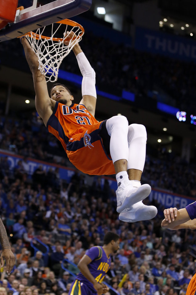 Photo - Oklahoma City's Andre Roberson (21) hangs on to the basket after a dunk during the NBA basketball game between the Oklahoma City Thunder and the New Orleans Pelicans at the Chesapeake Energy Arena, Saturday, Feb. 25, 2017.  Photo by Sarah Phipps, The Oklahoman