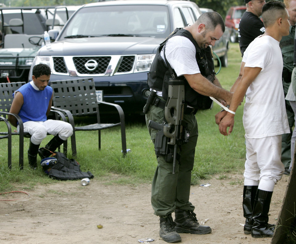 Photo - A State Trooper processes a jockey (right) while another waits in the background during a raid on a suspected illegal horse racing operation near Thackerville, OK., on Sunday, July 29, 2007. By John Clanton, The Oklahoman
