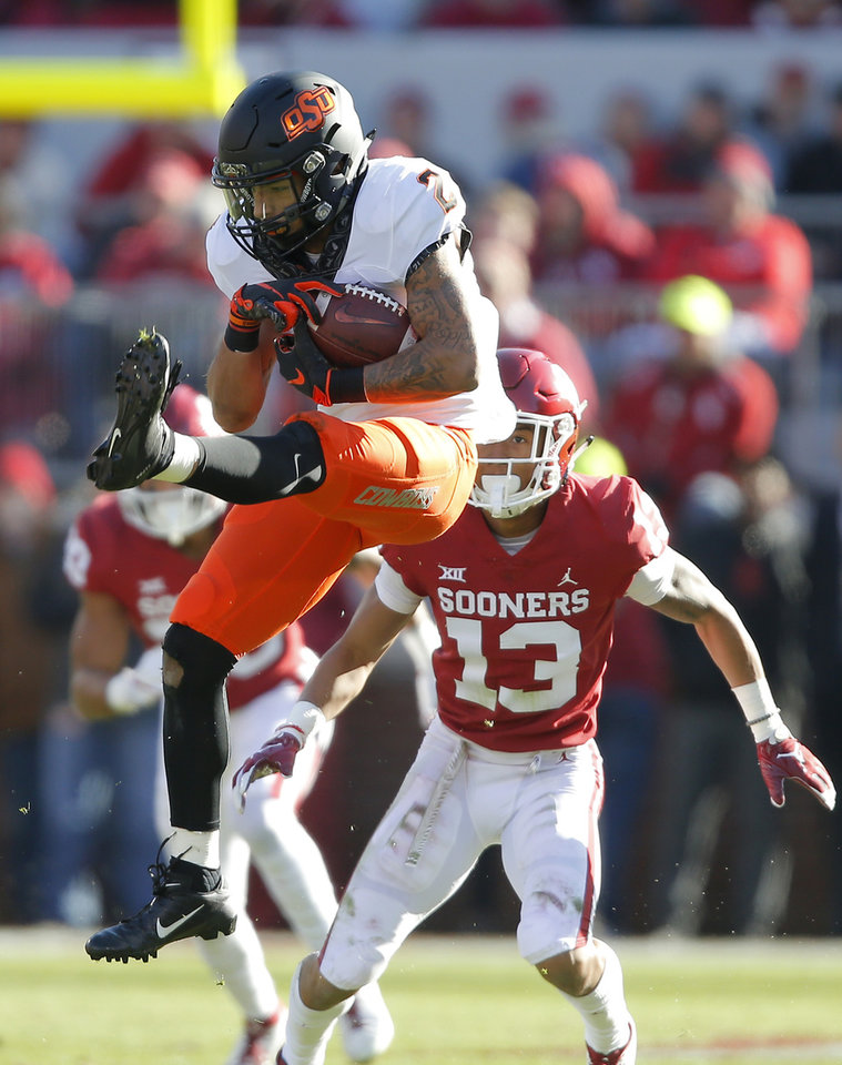 Photo - Oklahoma State's Tylan Wallace (2) catches a pass in front of Oklahoma's Tre Norwood (13) during a Bedlam college football game between the University of Oklahoma Sooners (OU) and the Oklahoma State University Cowboys (OSU) at Gaylord Family-Oklahoma Memorial Stadium in Norman, Okla., Nov. 10, 2018.  Photo by Bryan Terry, The Oklahoman
