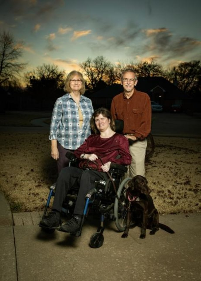 Photo -  Leah Campbell with her parents, Theresa and Don, and her service dog, Seaclaid, at their home in Mustang. [Photo provided]