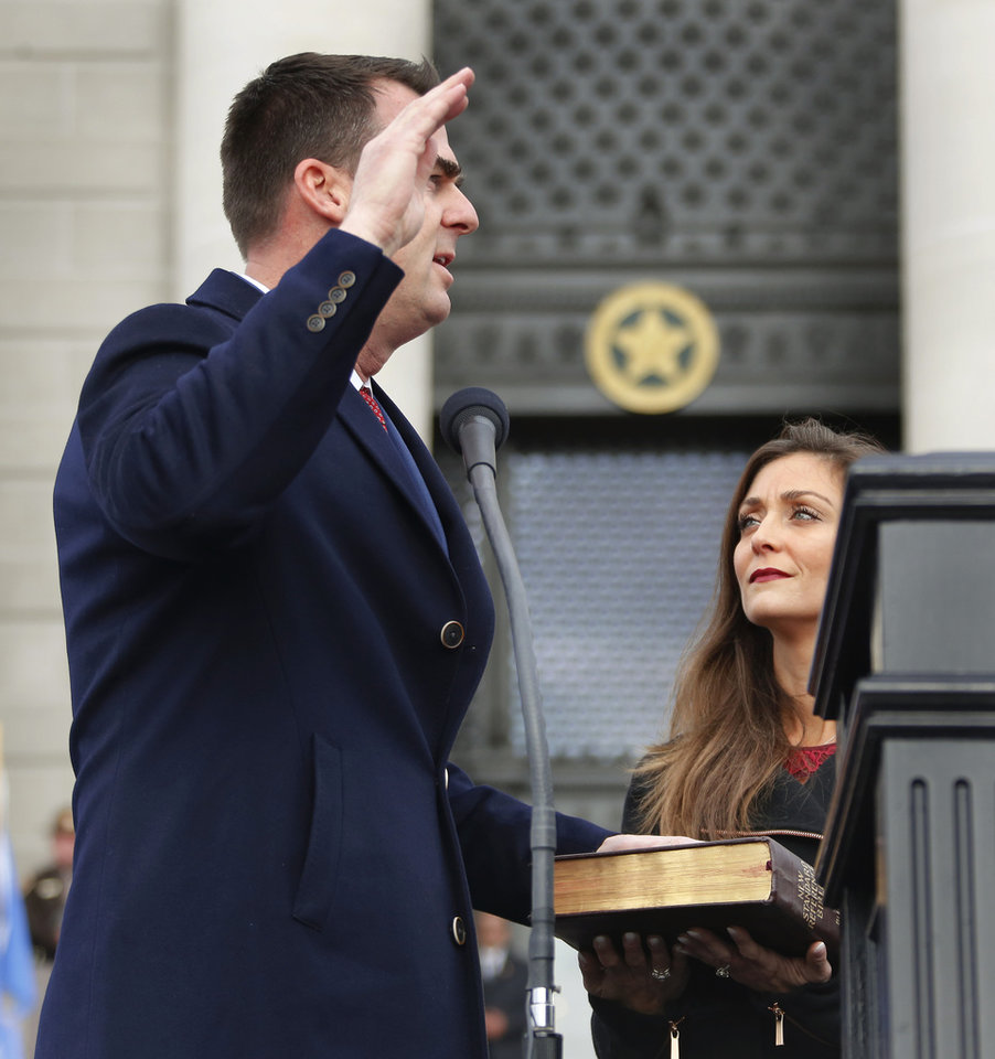 Photo - With his wife, Sarah, holding a Bible,  Kevin Stitt is sworn in as Oklahoma's 28th governor by Supreme Court Chief Justice Noma Gurich on Monday, Jan. 14, 2019. Photo by Jim Beckel, The Oklahoman.