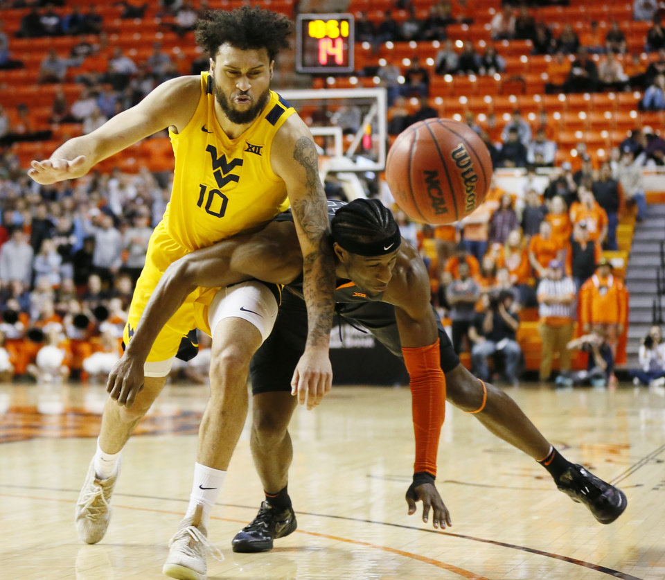 Photo - West Virginia's Jermaine Haley (10) and Cameron McGriff (12) collide in the first half during a men's college basketball game between the Oklahoma State Cowboys and West Virginia Mountaineers at Gallagher-Iba Arena in Stillwater, Okla., Monday, Jan. 6, 2020. [Nate Billings/The Oklahoman]