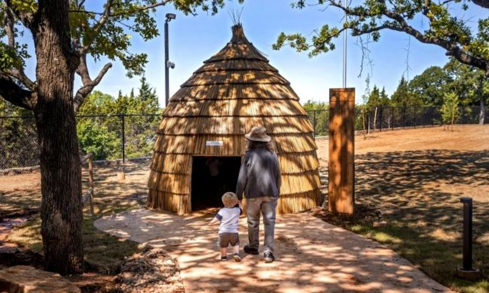 Photo -  Joyce Hopper and her grandson Aiden Turk check out the intertribal Native village that is part of the newly opened Liichokoshkomo', a $15 million outdoor attraction at the National Cowboy & Western Heritage Museum.[Chris Landsberger/The Oklahoman]