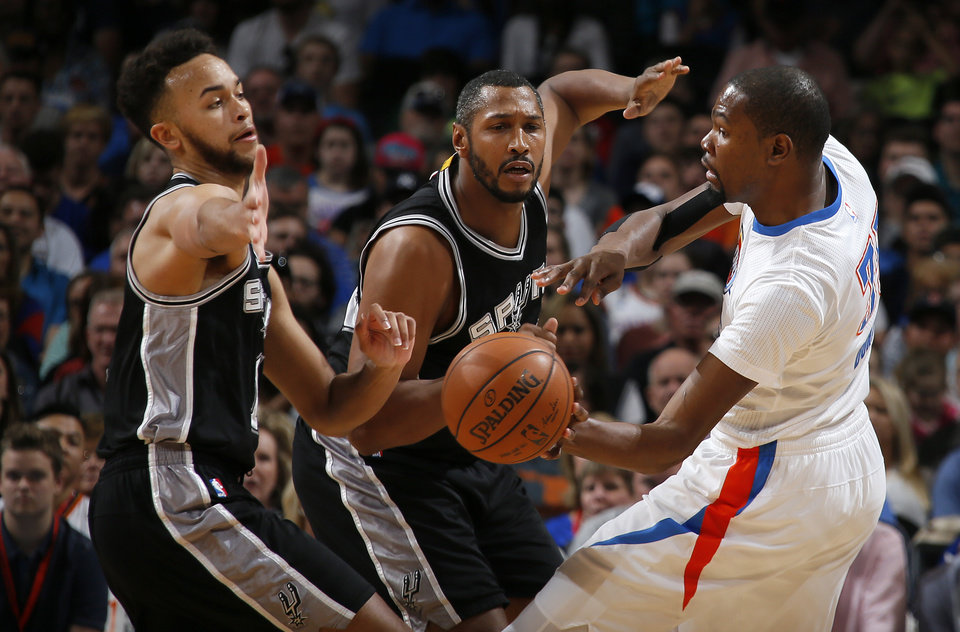 Photo - Oklahoma City's Kevin Durant (35) passes around San Antonio's Boris Diaw (33), center, and Kyle Anderson (1) during an NBA basketball game between the Oklahoma City Thunder and the San Antonio Spurs at Chesapeake Energy Arena in Oklahoma City, Saturday, March 26, 2016. Photo by Bryan Terry, The Oklahoman