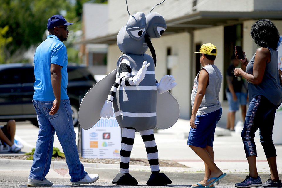 Photo - Tito the Mosquito with the OKC-County Health Department greets visitors during the oNE OKC annual street festival hosted Northeast OKC Renaissance Inc. in Oklahoma City, Saturday, June 8, 2019. [Bryan Terry/The Oklahoman]