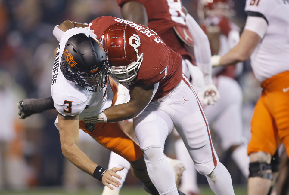 Photo - Oklahoma's Ronnie Perkins (7) hits Oklahoma State's Spencer Sanders (3) after a pass Saturday at Owen Field in Norman. [Bryan Terry/The Oklahoman]