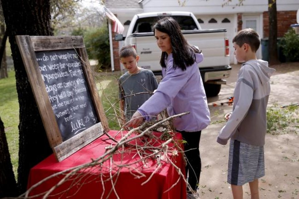 Photo -  Stephanie Stovall and her sons Nathan, 9, left, and Blake, 10, gather sticks while working outside their Edmond home to assembe a scene for a drive-thru Stations of the Cross. [Bryan Terry/The Oklahoman]