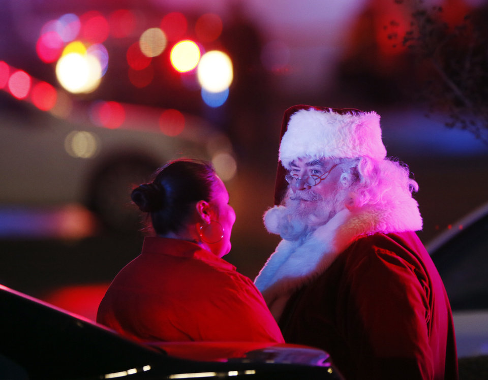Photo - Santa Claus waits near a police car after being evacuated from Penn Square Mall following a shooting inside the mall in Oklahoma City, Thursday, Dec. 19, 2019. [Nate Billings/The Oklahoman]