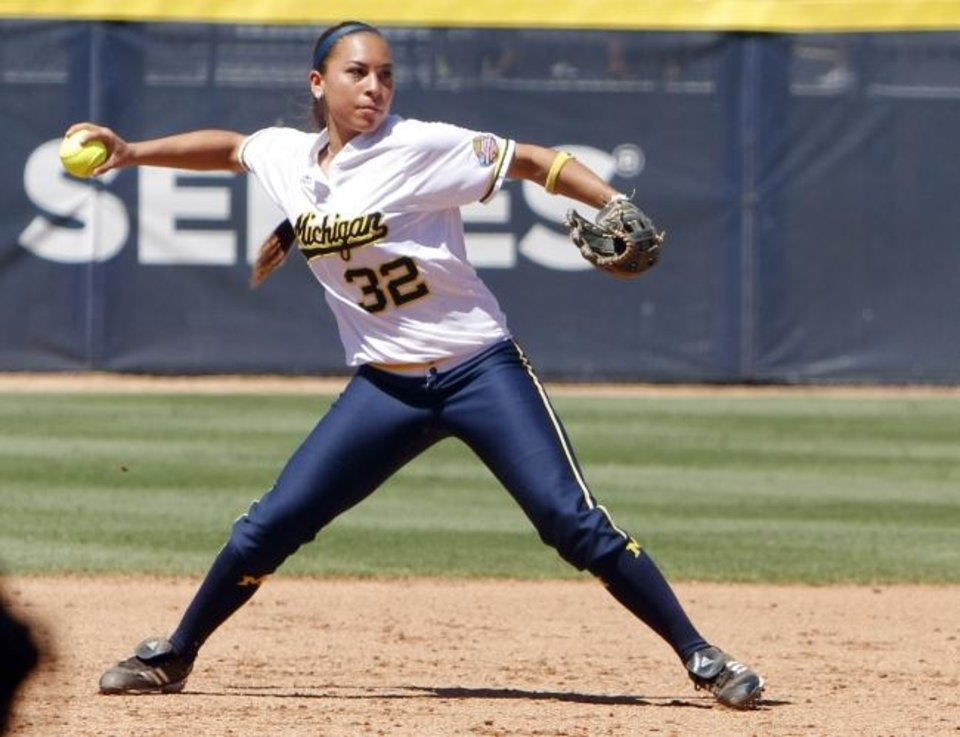 Photo -  Former Michigan shortstop Sierra Romero throws to first base in the Women's College World Series in 2013. Romero never won a national championship with the Wolverines, while sister Sydney has won two with Oklahoma. [OKLAHOMAN ARCHIVES]