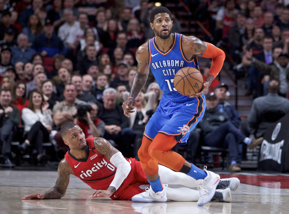 Photo - Oklahoma City Thunder forward Paul George, right, dribbles away from Portland Trail Blazers guard Damian Lillard during the first half of an NBA basketball game in Portland, Ore., Friday, Jan. 4, 2019. (AP Photo/Craig Mitchelldyer)