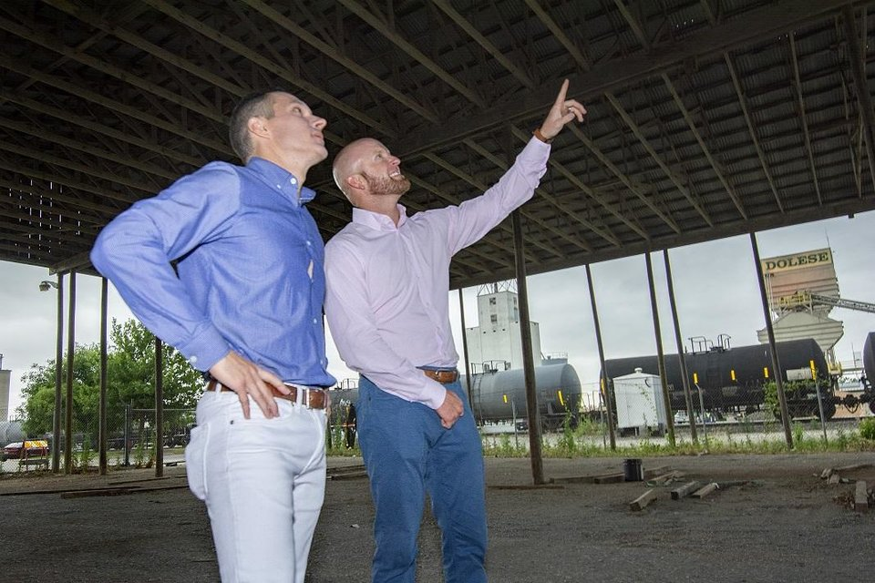 Photo -  Casey Massegee and Chris Anderson discuss their plans for redevelopment of an old lumberyard into a food and beer hall. [Photo by Eriech Tapia for The Oklahoman]