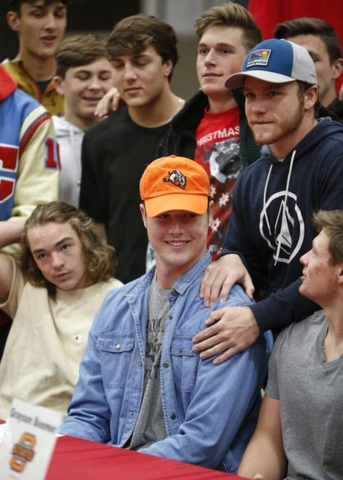 Photo -  Collinsville's Grayson Boomer, center, is surrounded by friends during a signing ceremony at Collinsville High School in December 2018. Boomer, who signed with Oklahoma State, announced Monday that he is transferring. [Matt Barnhard/Tulsa World]