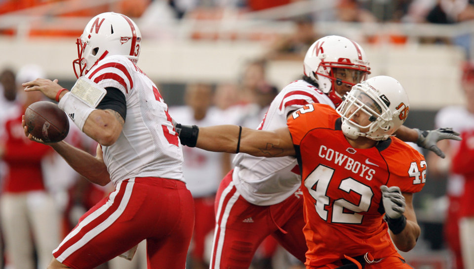 Photo - OSU's Justin Gent pressures Nebraska quarterback Taylor Martinez during the college football game between the Oklahoma State Cowboys (OSU) and the Nebraska Huskers (NU) at Boone Pickens Stadium in Stillwater, Okla., Saturday, Oct. 23, 2010. Photo by Sarah Phipps, The Oklahoman
