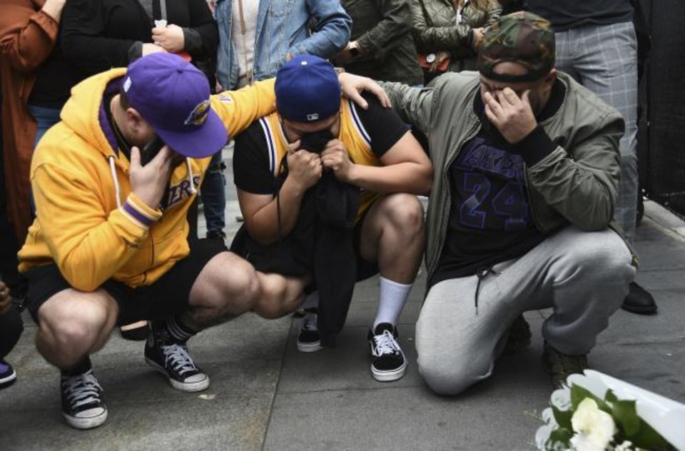 Photo -  Los Angeles Laker fans, from left, Alex Fultz, Eddy Rivas and Rene Alfaro mourn retired NBA star Kobe Bryant outside of the Staples Center on Sunday in Los Angeles. [Chris Pizzello/The Associated Press]