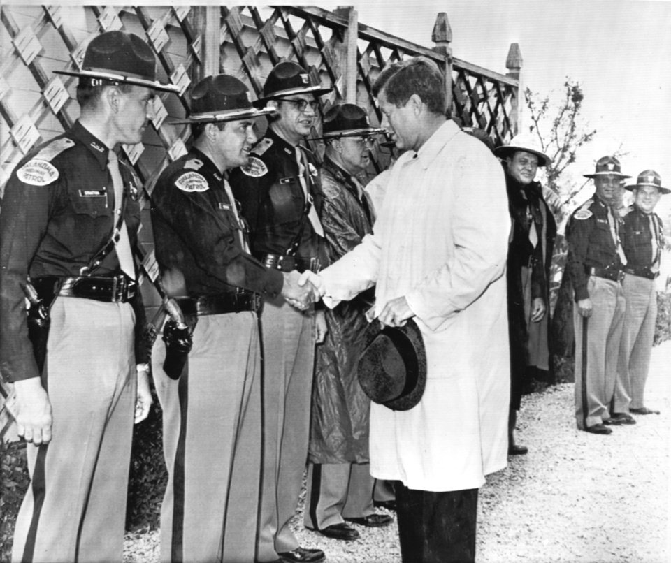 Photo - President Kennedy bids some Oklahoma state troopers farewell in a pouring rain as he prepares to leave the ranch home of Sen. Robert S. Kerr where he was a house guest. AP Photo