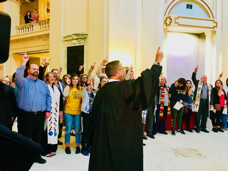 Photo - The Rev. Mitch Randall encourages the crowd to hold up their index finger to represent their plan to use their their