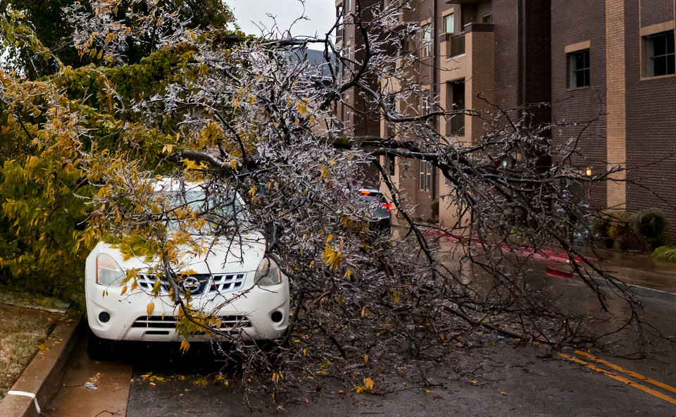 Photo - A broken tree covers a car in Oklahoma City, Okla. on Tuesday, Oct. 27, 2020, after a winter blast covered the state with ice.  [Chris Landsberger/The Oklahoman]