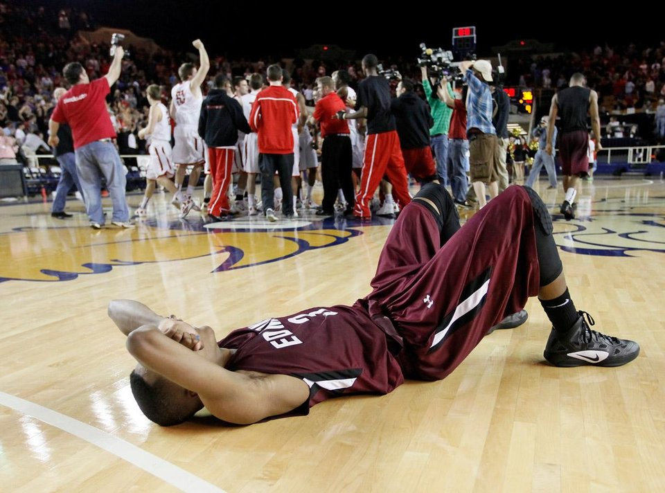 Photo -  Edmond Memorial's James Woodard (3) lies on the court as the Union Redskins celebrate after the Class 6A boys high school basketball state tournament championship game between Edmond Memorial and Tulsa Union at the Mabee Center in Tulsa, Okla., Saturday, March 10, 2012. Union won, 37-36. Photo by Nate Billings, The Oklahoman
