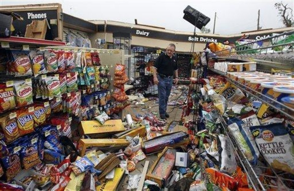 Photo - Warren Waltz, of Love's, examines tornado damage to the store at Choctaw Road and Interstate 40 east of Oklahoma City today. AP Photo