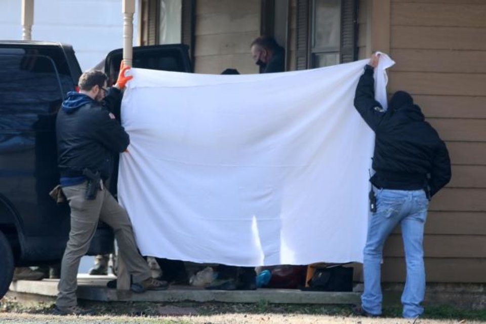Photo -  Investigators block the public's view as bodies are removed from the scene of a suspected mass homicide where at least 5 children were slain Tuesday, Feb. 2, 2021 in Muskogee, Okla. [Photo by Mike Simons, Tulsa World]