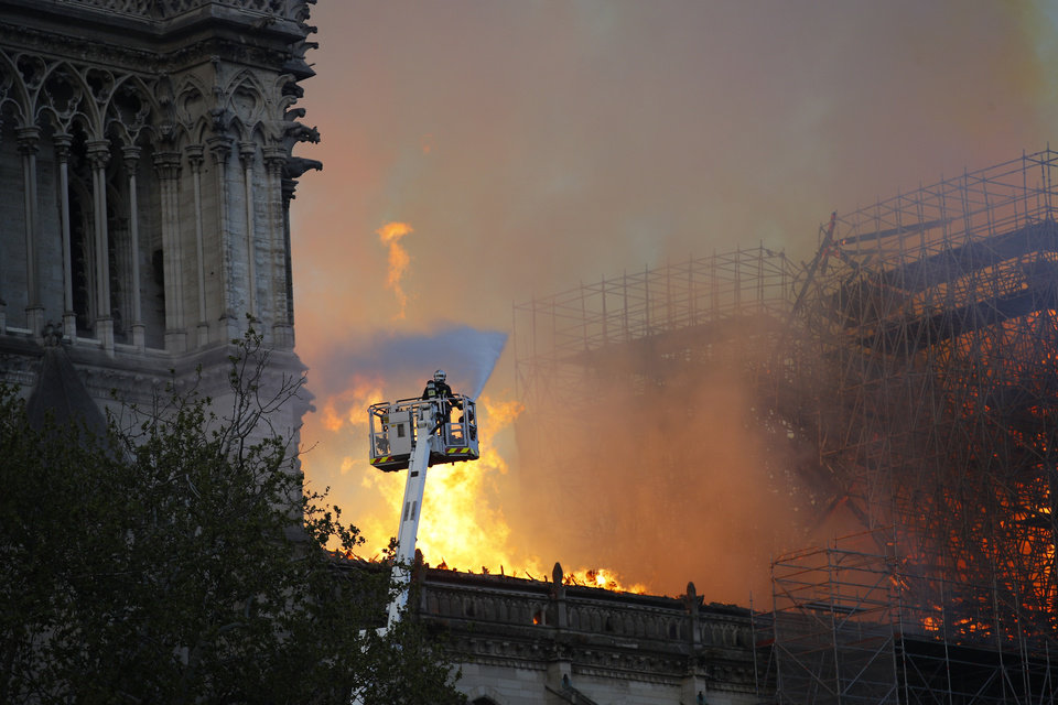 Photo - A firefighter uses a hose as Notre Dame cathedral burns in Paris, Monday, April 15, 2019. A catastrophic fire engulfed the upper reaches of Paris' soaring Notre Dame Cathedral as it was undergoing renovations Monday, threatening one of the greatest architectural treasures of the Western world as tourists and Parisians looked on aghast from the streets below. (AP Photo/Francois Mori)