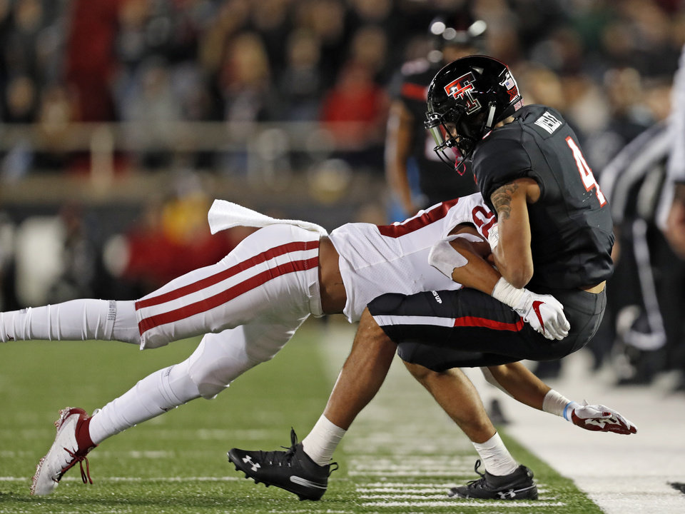 Photo - Texas Tech's Antoine Wesley (4) is tackled by Oklahoma's Robert Barnes during the second half of an NCAA college football game Saturday, Nov. 3, 2018, in Lubbock, Texas. (AP Photo/Brad Tollefson)