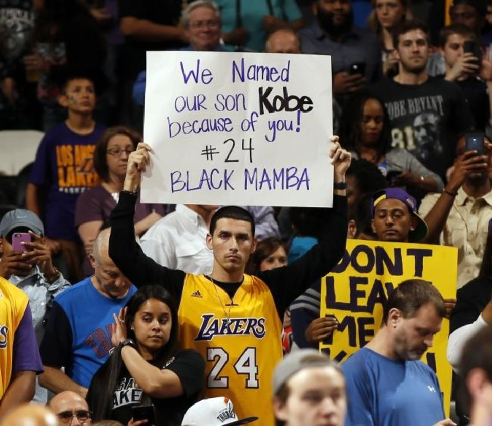 Photo -  A fan holds a sign for Kobe Bryant during warmups before an April 2016 game between the Oklahoma City Thunder and the Los Angeles Lakers at Chesapeake Energy Arena. Bryant died Sunday at age 41 in a helicopter crash. [Nate Billings/The Oklahoman]