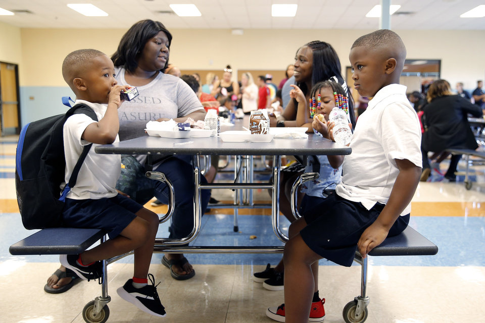 Photo - Brothers Jeffery Hamilton , 4, in pre-K, left, and first-grader Jaxson, 6, eat breakfast with their mother Olivia Hamilton, left, aunt Tashera Ragsdale, and sister Jazzy Hamilton, 3, inside Britton Elementary during the first day of school in Oklahoma City, Monday, Aug. 12, 2019. [Bryan Terry/The Oklahoman]