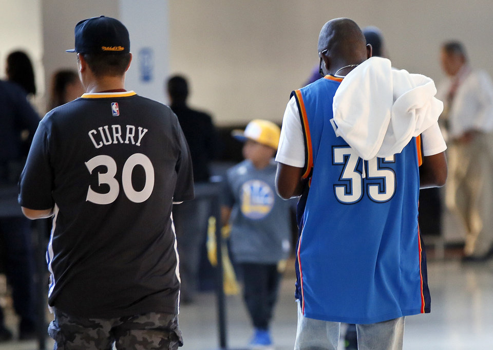 Photo - Thunder fan Henry Crockett, right, of Las Vegas, walks next to a Golden State fan before Game 2 of the Western Conference finals in the NBA playoffs between the Oklahoma City Thunder and the Golden State Warriors at Oracle Arena in Oakland, Calif., Wednesday, May 18, 2016. Crockett became a fan of Kevin Durant because he also grew up in the Washington D.C. area. Photo by Nate Billings, The Oklahoman