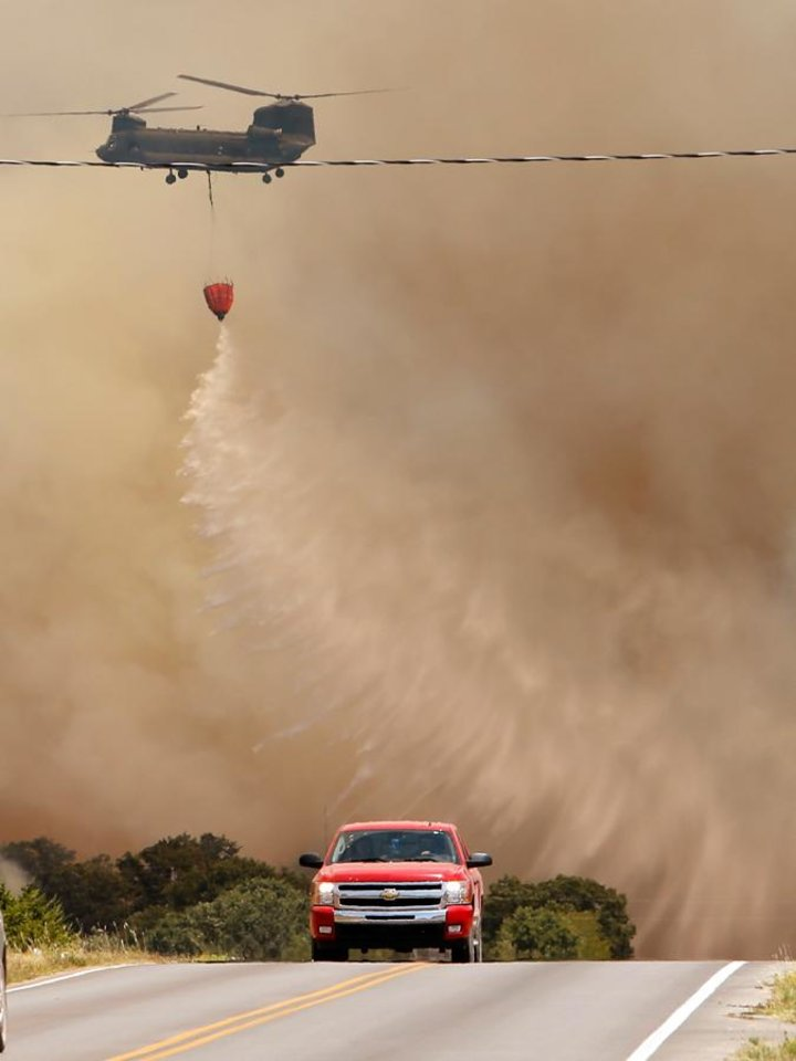 Photo -  A Helicopter drops water on a large grass fire east of 120th near Cemetery Road on Friday, Aug. 3, 2012, east of Norman, Okla.  Photo by Steve Sisney, The Oklahoman