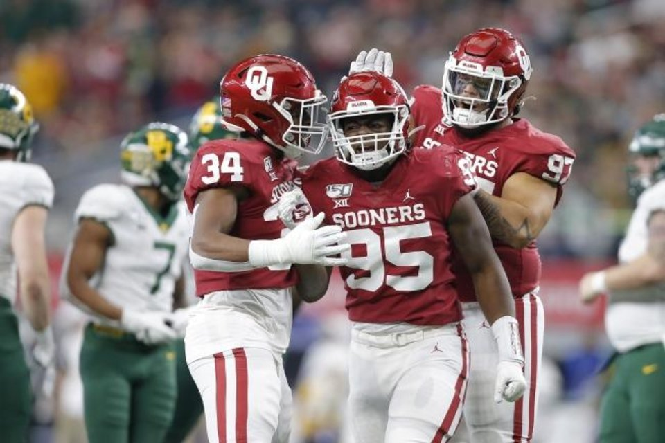 Photo -  David Ugwoegbu (34), Isaiah Thomas (95) and Marquise Overton (97) celebrate during the Sooners' 30-23 win against Baylor in last season's Big 12 title game. [Bryan Terry/The Oklahoman]