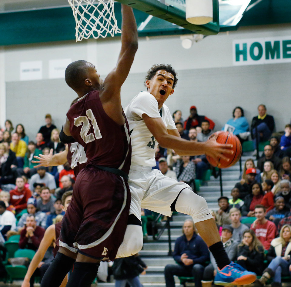 Photo - Fueled by the scoring of junior guard Trae Young, shown here going for a lay-up against Edmond defender Kristian Doolittle, the Norman North Timberwolves defeated the Edmond Memorial Bulldogs , 77-64, to win the championship game of the 56th Annual McGuinness Classic basketball tournament Saturday night, Jan. 9, 2016.   Photo by Jim Beckel, The Oklahoman.