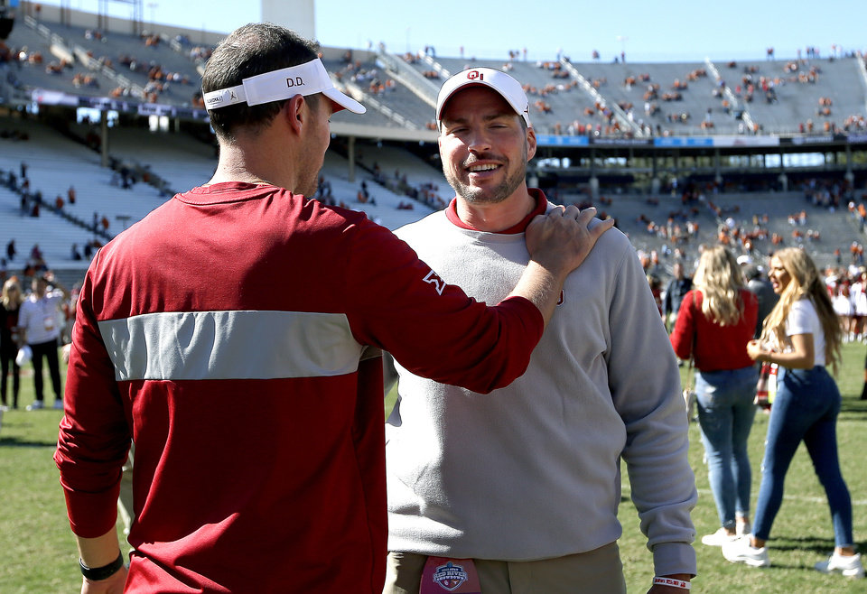 Photo - Oklahoma head coach Lincoln Riley and Alex Grinch talk following the Red River Showdown college football game between the University of Oklahoma Sooners (OU) and the Texas Longhorns (UT) at Cotton Bowl Stadium in Dallas, Saturday, Oct. 12, 2019. OU won 34-27. [Sarah Phipps/The Oklahoman]