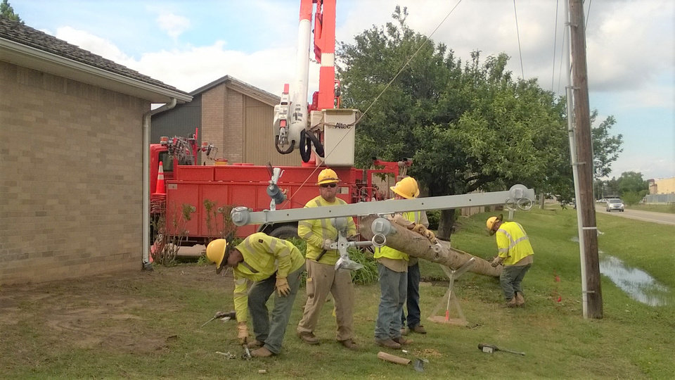 Photo -  An OG&E crew works installs a new pole and cross-arm during a response to a storm that affected the utility's service area in Enid in 2017. Officials said the utility lost 115 poles and 215 cross-arms in severe storms that impacted Oklahoma this past weekend. [Photo provided by OG&E]