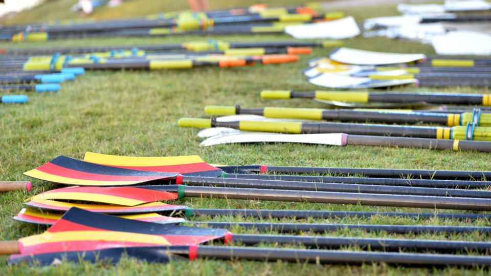 Photo -  Oars are lined up on the grass by the loading docks. [PHOTO BY JACKIE DOBSON, FOR THE OKLAHOMAN]