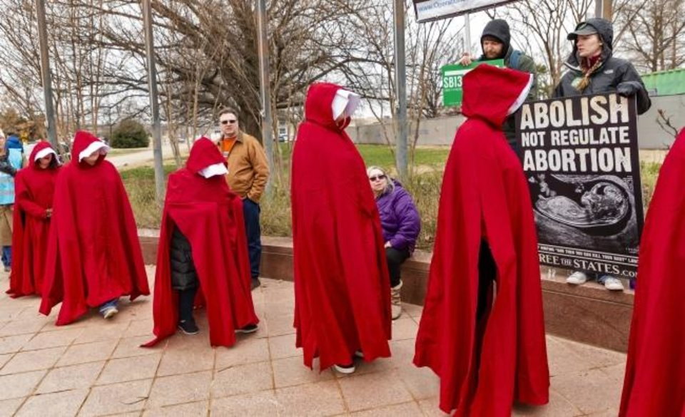 Photo -  Pro-choice supporters dressed in handmaid attire walk to the State Capitol past pro-life supporters on Tuesday at the State Capitol. [Chris Landsberger/The Oklahoman]