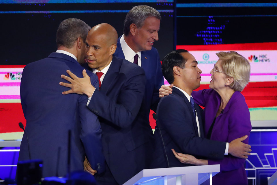 Photo - Democratic presidential candidate Sen. Cory Booker, D-N.J., second from left, hugs Rep. Tim Ryan, D-Ohio, while Sen. Elizabeth Warren, D-Mass., hugs former Housing and Urban Development Secretary Julian Castro at the end of a Democratic primary debate hosted by NBC News at the Adrienne Arsht Center for the Performing Arts, Wednesday, June 26, 2019, in Miami. In between them is New York City Mayor Bill de Blasio. (AP Photo/Wilfredo Lee)