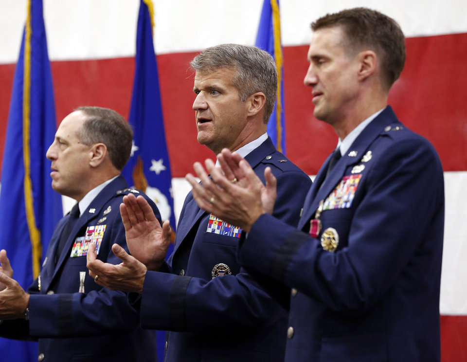 Photo -  Air Force Sustainment Center Commander Lt. Gen. Lee K. Levy II, left, Brig. Gen. Christopher D. Hill, and Brig. Gen. Tom D. Miller clap and sing the Air Force song during the Oklahoma City Air Logistics Complex change of command ceremony at Tinker Air Force Base on Monday. [Photo by Steve Sisney, The Oklahoman]