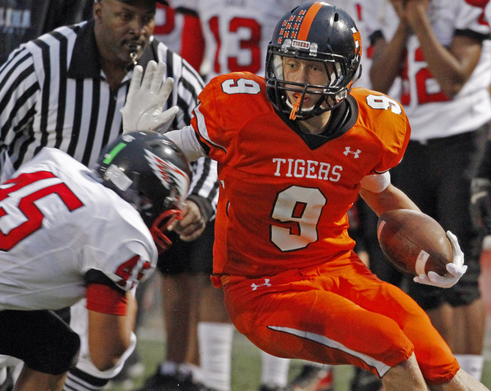 Photo -  Norman's George Kittle (9) tries to stay in bounds as Del City's Gabriel Deluna bears down during a game in Norman on Sept. 15, 2011. [PHOTO BY STEVE SISNEY, THE OKLAHOMAN]