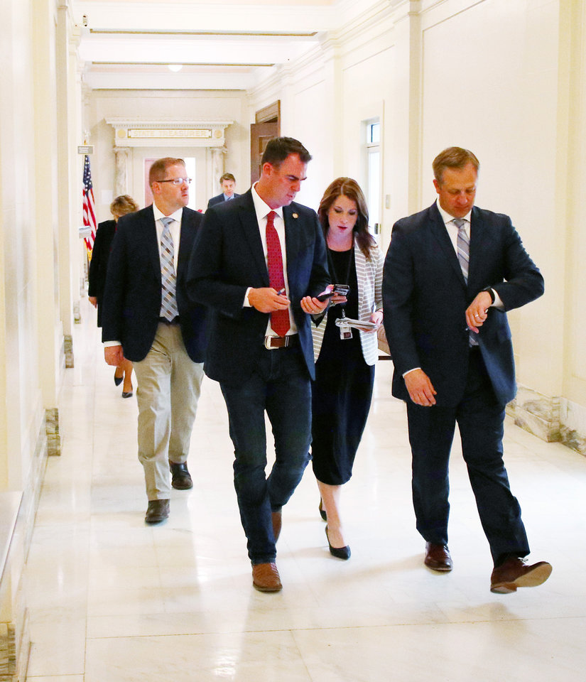 Photo - Gov. Kevin Stitt and staff leave the Blue Room of the Capitol after signing the budget, Friday , May 24, 2019. [Doug Hoke/The Oklahoman]