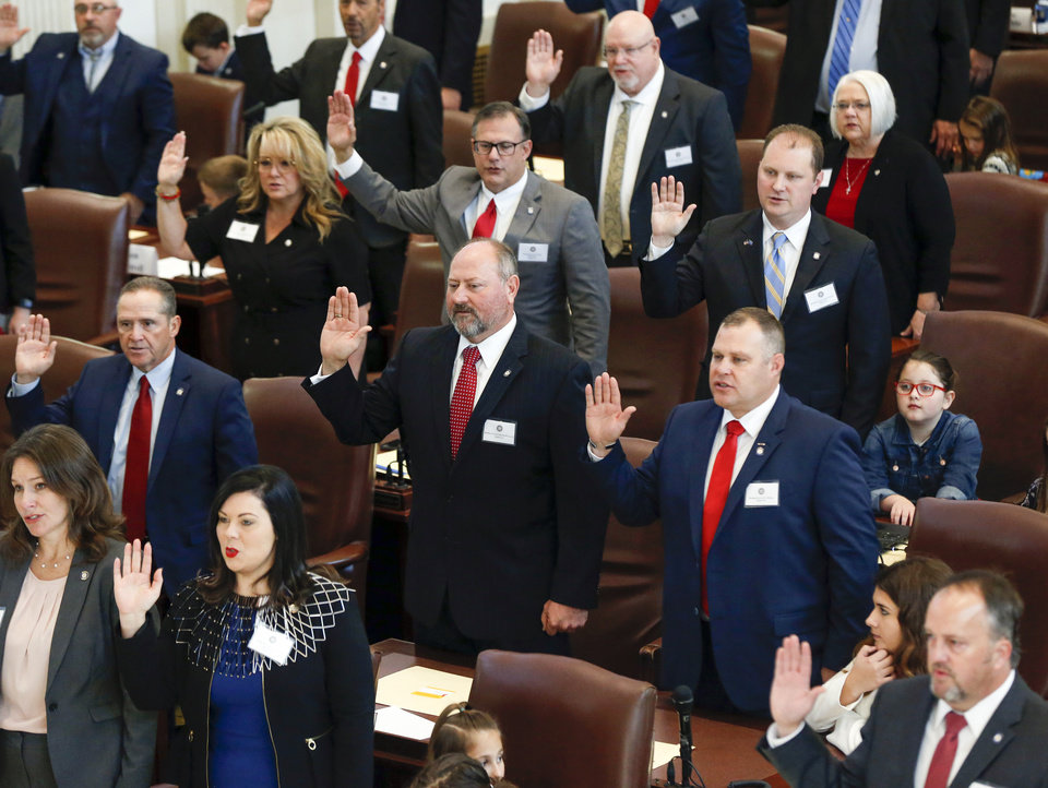 Photo -  Newly elected members of the Oklahoma House of Representatives take the oath of office in the House chamber on Wednesday. [Photo by Nate Billings, The Oklahoman]
