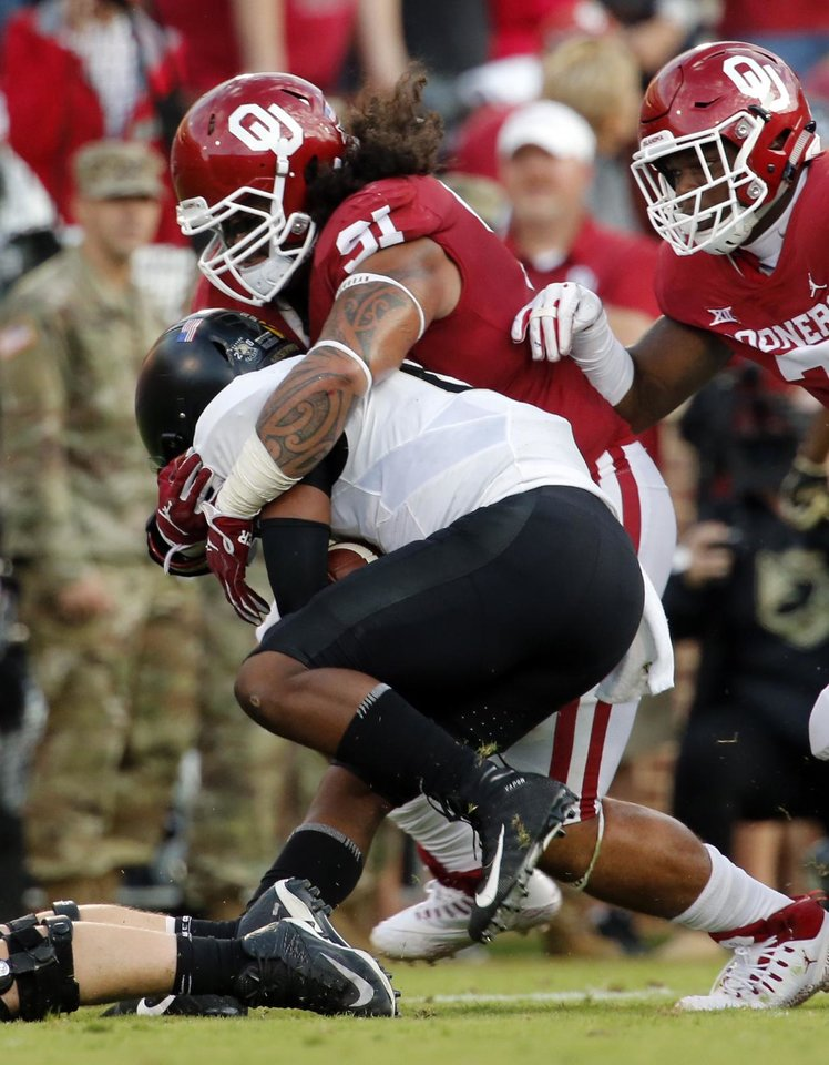 Photo - Oklahoma's Dillon Faamatau (91) brings down quarterback Kelvin Hopkins Jr. (8) during a college football game between the University of Oklahoma Sooners (OU) and the Army Black Knights at Gaylord Family-Oklahoma Memorial Stadium in Norman, Okla., on Saturday, Sept. 22, 2018. Photo by Steve Sisney, The Oklahoman