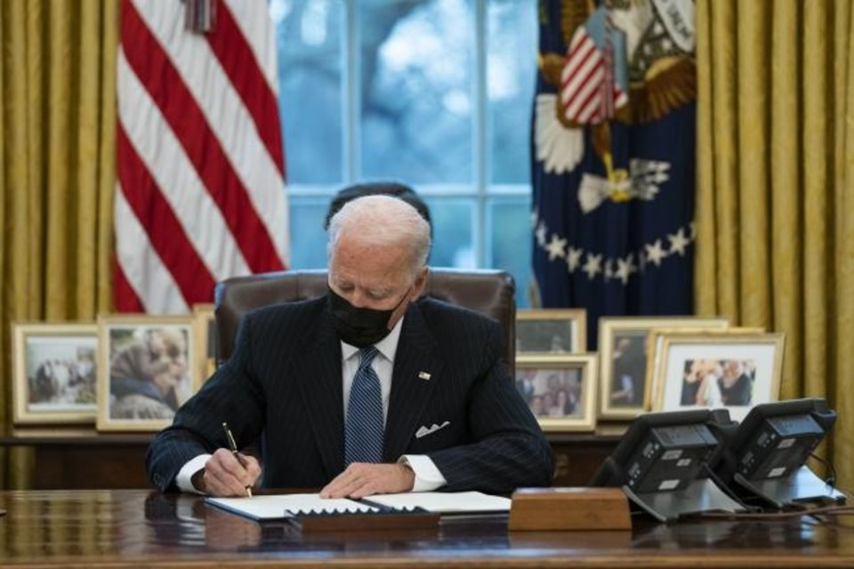 Photo -  President Joe Biden signs an Executive Order reversing the Trump era ban on transgender individuals serving in military in the White House's Oval Office. On Wednesday, Biden issued a series of executive orders that impact oil and gas leasing activities involving minerals owned by the federal government. [AP Photo/Evan Vucci]