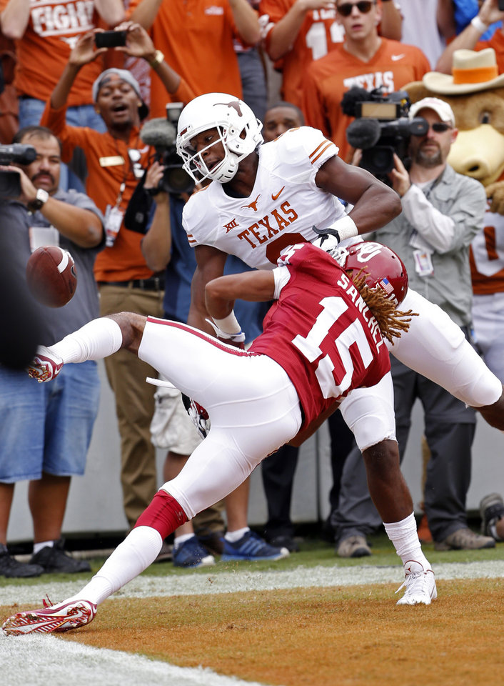 Photo - Oklahoma's Zack Sanchez (15)defends on a pass in the end zone to Texas' John Harris (9) during the Red River Showdown college football game between the University of Oklahoma Sooners (OU) and the University of Texas Longhorns (UT) at the Cotton Bowl in Dallas, Texas on Saturday, Oct. 11, 2014. 