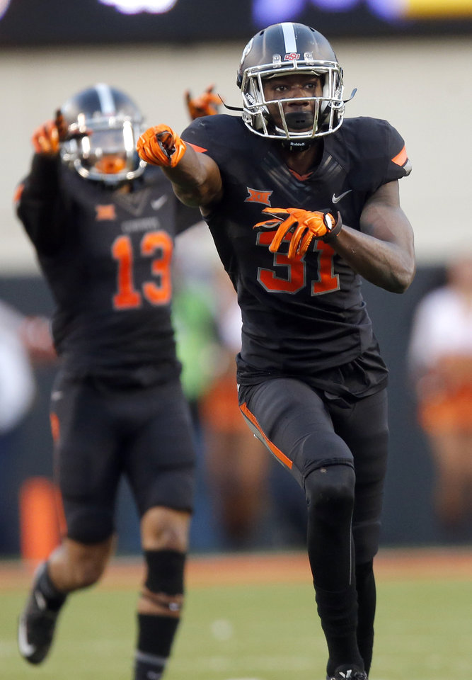 Photo - Oklahoma State's Tre Flowers (31) celebrates an interception during Saturday's game against TCU at Boone Pickens Stadium. The Cowboys moved up to No. 5 in the polls. (Photo by Sarah Phipps, The Oklahoman)