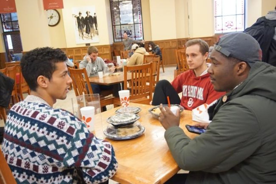 Photo -  Lustin Rainey, Noah Clark and Cameron Terry, students at the University of Oklahoma, sit inside the student union on campus in Norman. [Ben Felder/The Oklahoman]