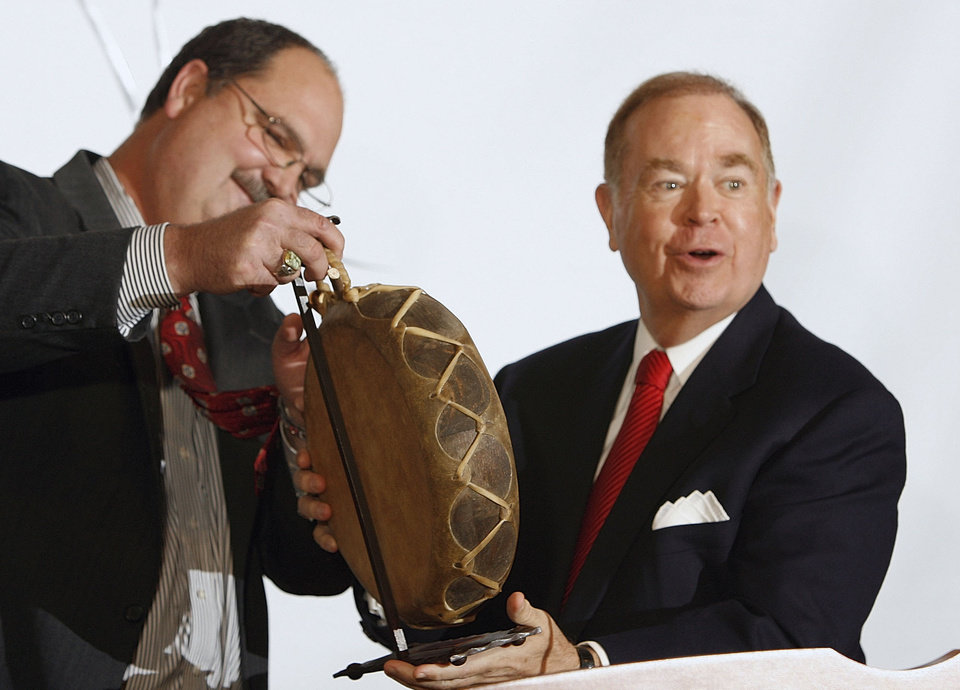 Photo - DONATION: David Boren, University of Oklahoma President, leaves the stage with an Indian drum and a promised gift from Don Cain (left), President of AT&T Oklahoma to encourage Oklahoma Native American Students to attend OU. The announcement was made at the Oklahoma History Center in Oklahoma City, Oklahoma on Tuesday, October 31, 2006. Photo by Steve Sisney/The Oklahoman ORG XMIT: kod